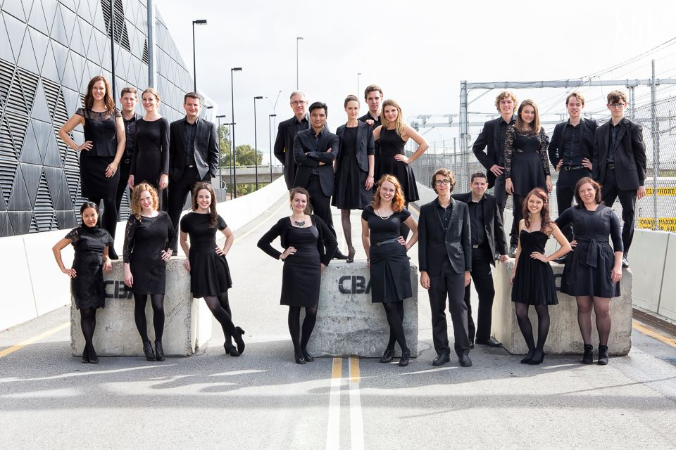 a group of young men and women dressed in black standing in an urban environment