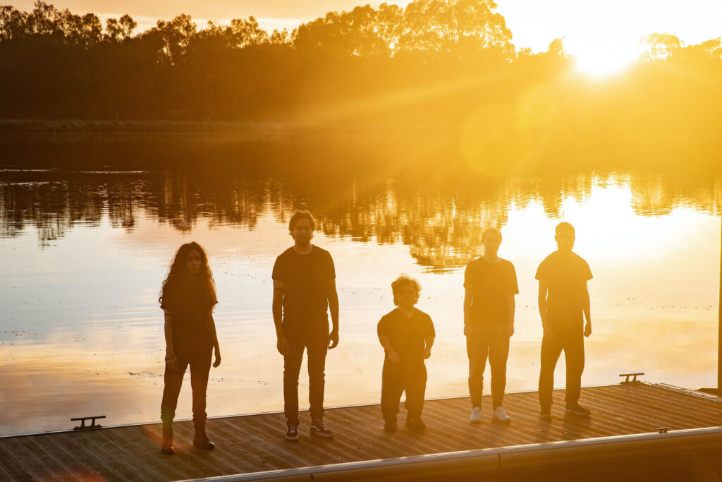 Five figures stand along the edge of the Swan River at sunset.