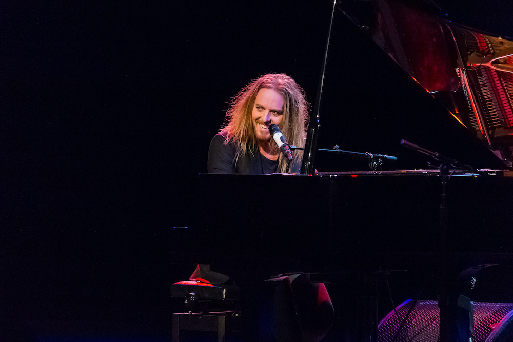 Tim Minchin sits on a lit stage, at a grand piano, with a wicked grin on his face.