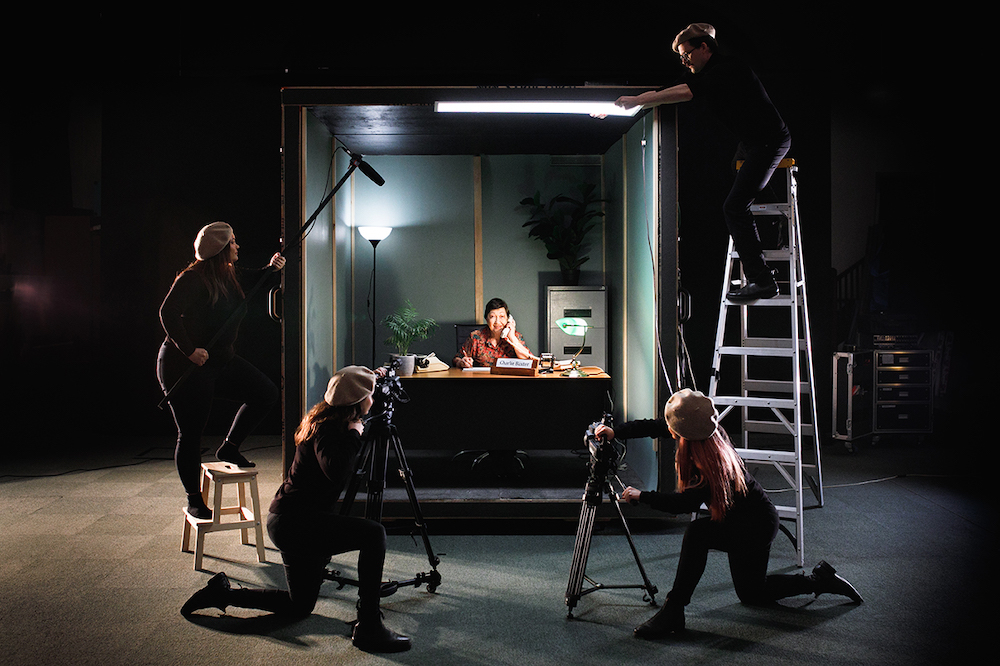 A scene from Whistleblower shows a person sitting in an office set, surrounded by film crew.