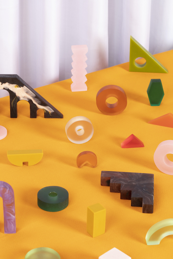 A series of colourful shapes made of what looks like resin. The shapes are things like doughnut rings, steps, heaxagons, and other more abstract shapes. They sit on a yellow surface, with a corrugated white back drop.