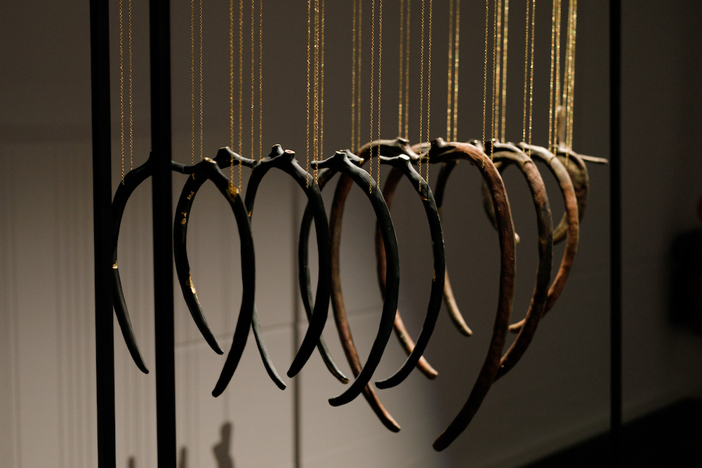 A line of porcelain ribs hands by gold chains.