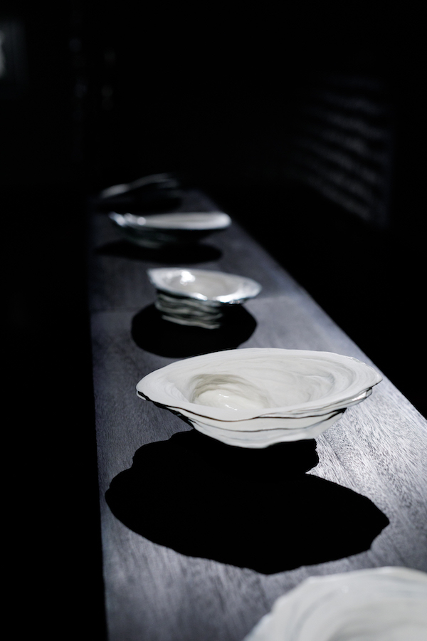 Four sculptures of oyster shells. The first is close to the camera lens, the others retreat behind it. The shells are smooth and creamy white against a black backdrop.