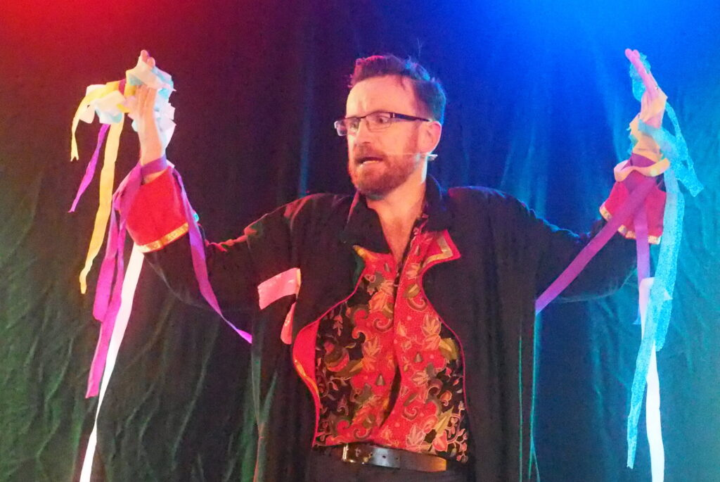 Tomas Ford stands on stage, his streamer-bedecked arms raised.