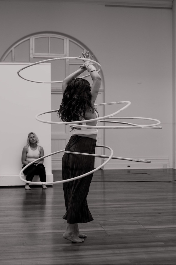 A woman stands with her back to the camera. She is twirling five hoops about her body, she is in motion and her arms are extended upwards. Another woman watches. They are both wearing light coloured tops and black loose pants. The image is black and white.