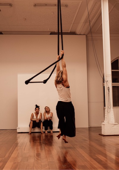 A woman hands from the ropes of a trapeze, which flings out behind her. Her back is to the camera. Two women watch her. They all wear white fitted tops and loose-fitting black pants.