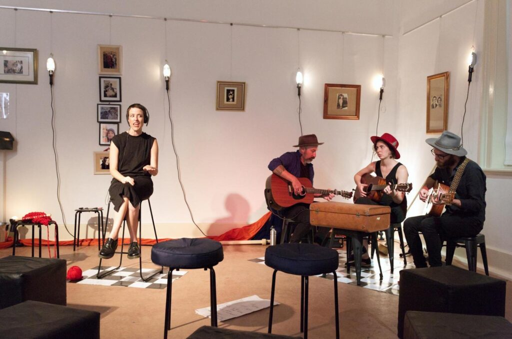 A woman sits on a stool. She wears headphones and appears to be speaking. To her left are a group of musicians, also seated. They are in a room, the walls of which are festooned with framed photographs.