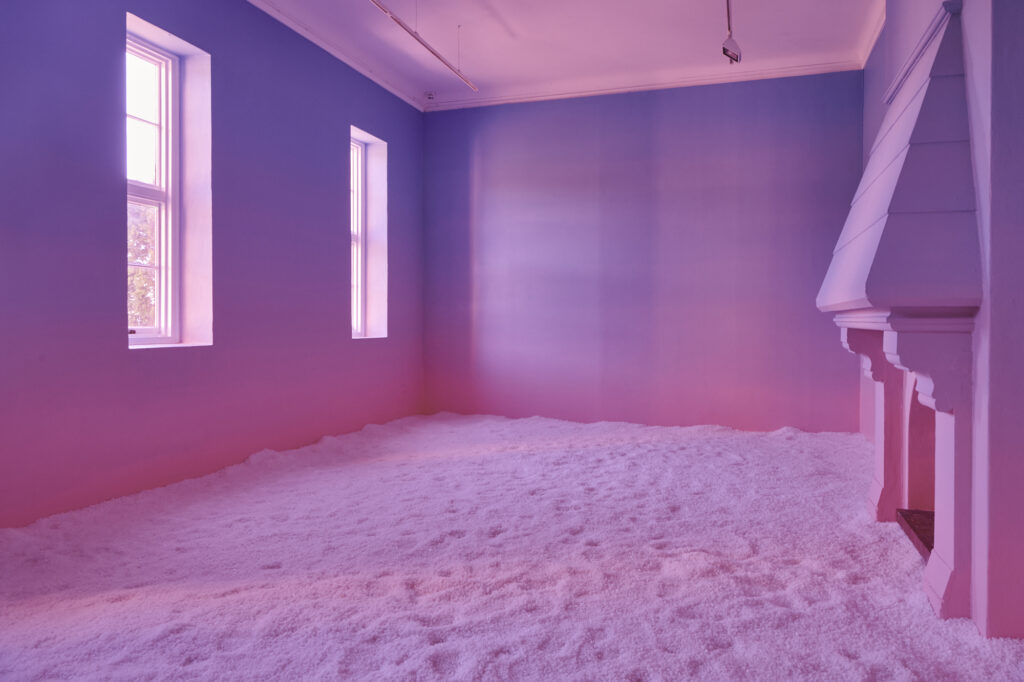 An empty room, with two sash windows and a fire place opposite. The room is lit pink and the floor is covered in a thick layer of salt.