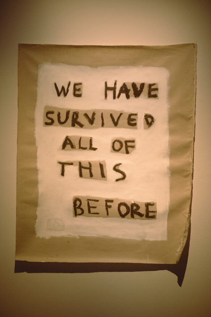 A canvas with the hand-painted words: WE HAVE SURVIVED ALL OF THIS BEFORE.