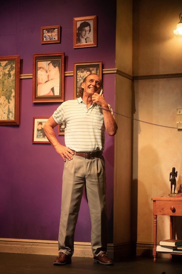 Bruce Denny, as Harry, stands with his legs firmly planted and one hand on his hip, as he talks on a 1980's landline phone that is mounted on the wall. He's smiling.