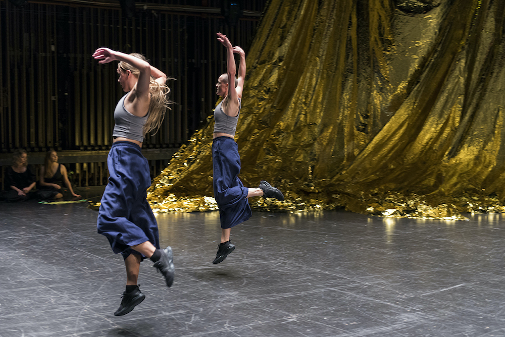 Francesca Fenton and Ella-Rose Trew are captured mid-motion, a few inches off the floor, their arms extended above their heads. In the background is the golden curtain.