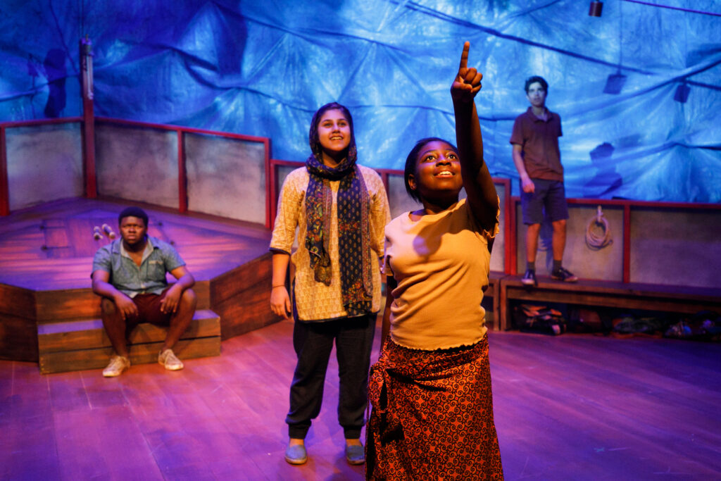 Four young people of colour stand on stage. At the front one young woman points hopefully at something out of shot. The set is the deck of a boat.