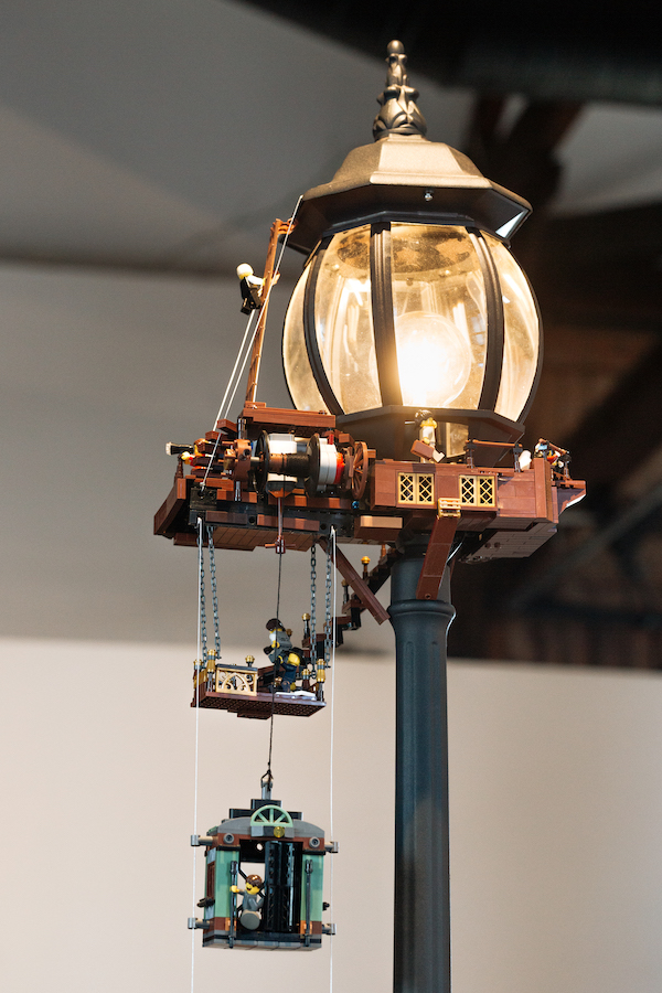 An old-fashioned lift, made of lego, hangs off an old fashioned lamp-post. above the lift is a platform, on which a minifig is working. The lamp light is switched on.