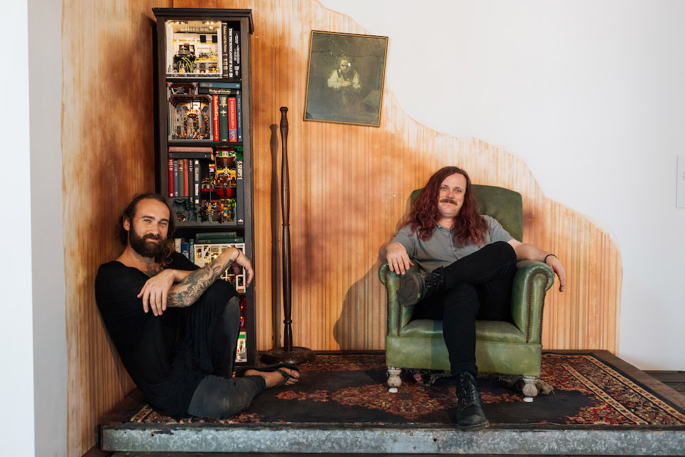 Jackson Harvey and Alex Towler sit in the corner of a room, Harvey on the floor, which is covered in a Persian rug, and Towler in a vintage lime green leather armchair. There is a narrow bookshelf in one corner, a lampstand with no lamp and a black and white portrait hanging on the wall.
