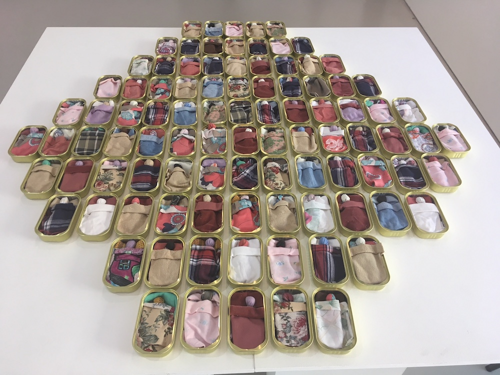 Sharyn Egan's work 'Our Babies' is comprised of rows of open sardine cans, each containing a blanket, covering a small fabric doll.