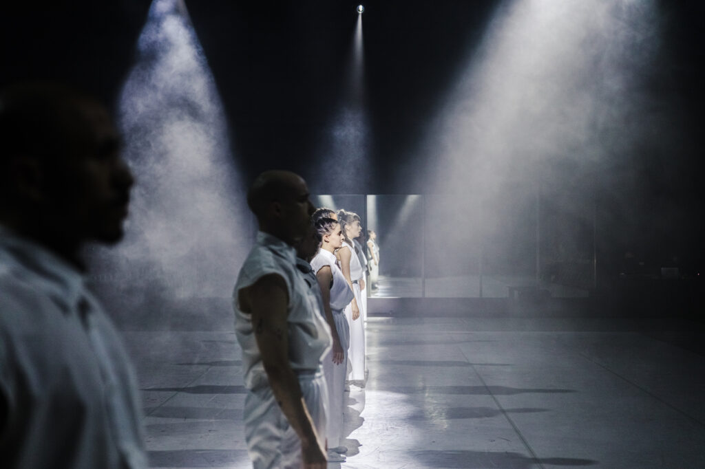 A line of dancers stands facing right. They are dressed in white and staring solemnly ahead. Shafts of haze filled light surround them.