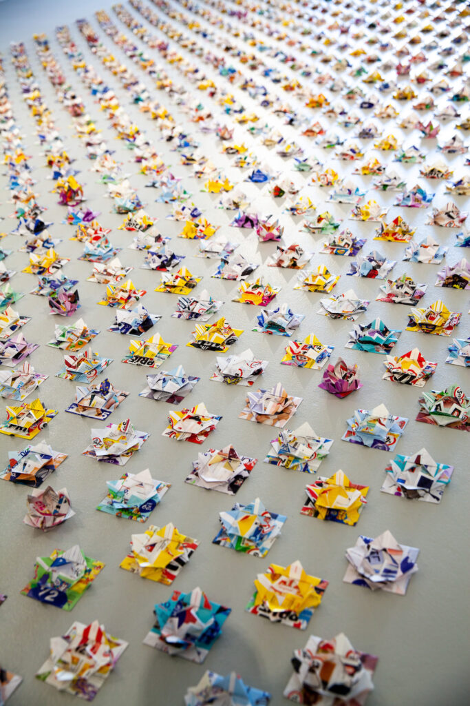 A sea of brightly coloured origami lotus flowers.