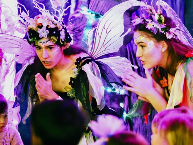 Two girls with wings, face painting and flowers in their hair lean forward to engage with the children in the foreground
