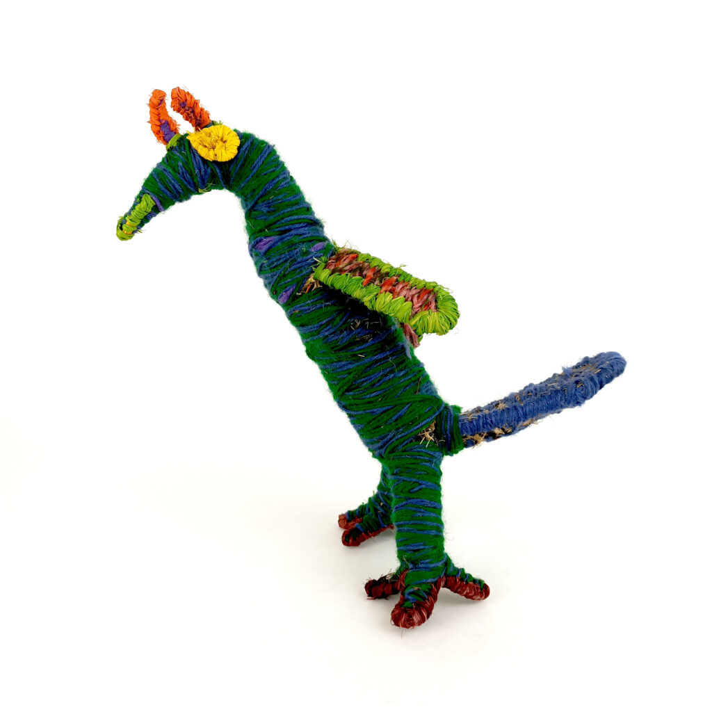 A bird sculpted in bright greens with splashes of yellow, blue and orange.