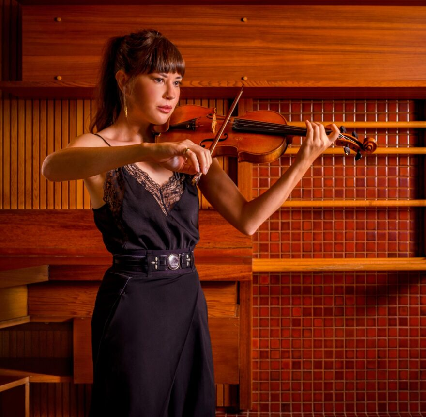 A girl wearing a dark dress plays violin in front of a backdrop of a wall of red and brown wood tones