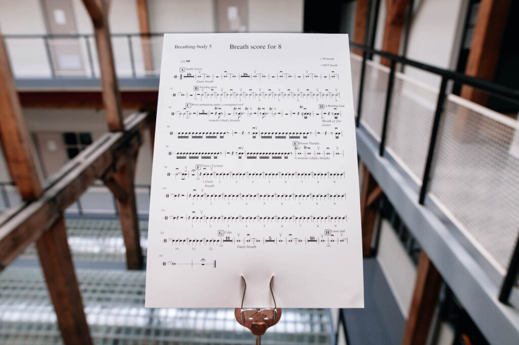 The music score for 'Breathing Backwards' sits on a music stand. It seems to be placed at the edge of a balcony.