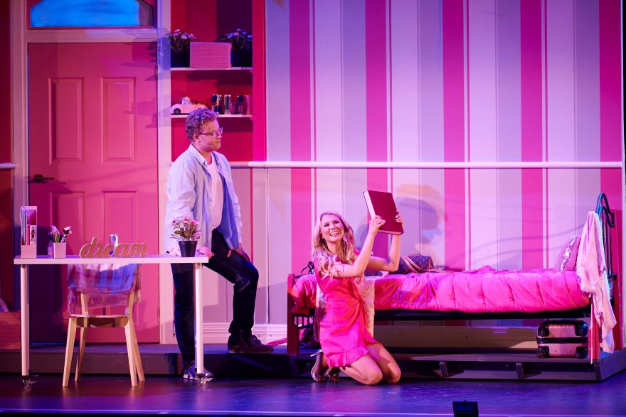 A man in casual jeans and shirt stands in a pink bedroom while a girl in pink kneels with a pink box in her hand