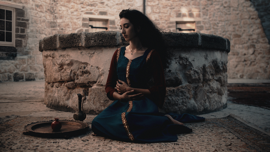 A woman dressed in a long teal coloured dress with crimson sleeves and gold trim kneels in front of a stone well. To her side is a small metal jug and a tray with a small vessel on it. Her hands are held gently in front of her and she looks down at the implements.