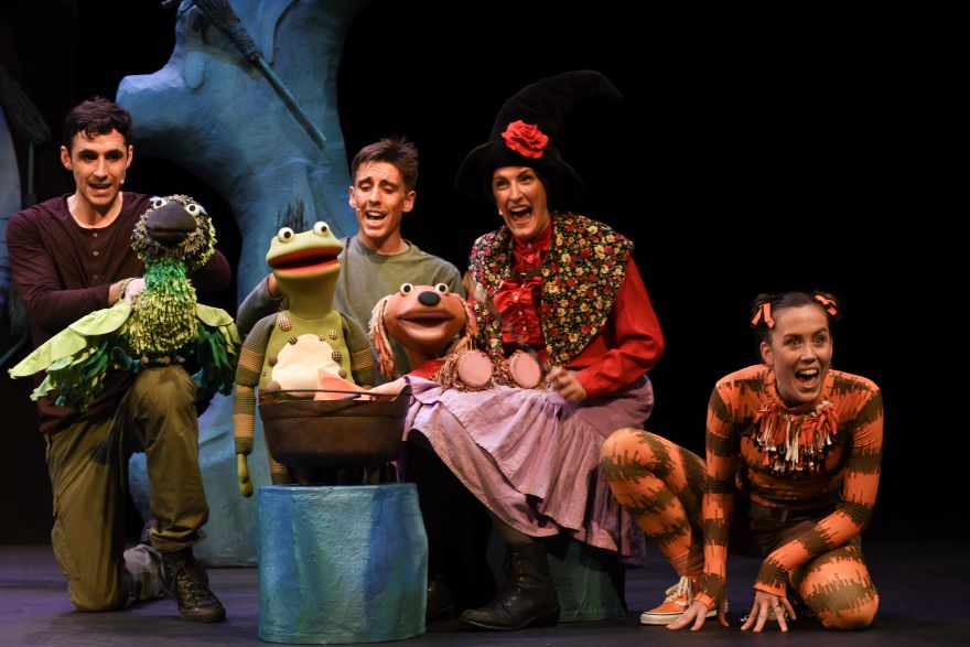 Four people crouch around a cauldron, holding bird, dog and frog puppets