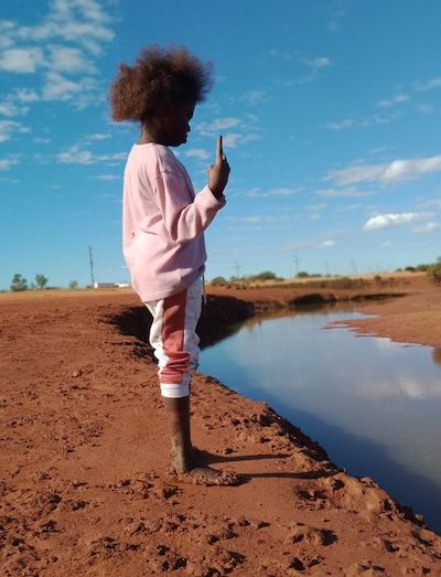 A young Aboriginal girl stands at the shore of a creek, holding up one finger. The ground is red, the sky blue and scatted with small clouds.