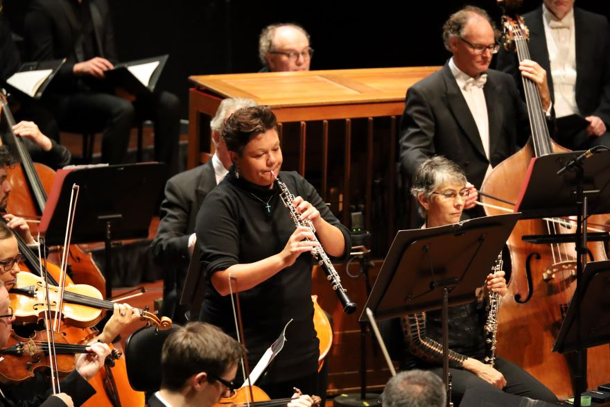 An oboe player stands to play a solo, her orchestral colleagues are seated around her on the stage.