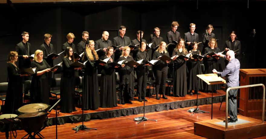 A 23-piece mixed gender choir stand in two lines across a stage, dressed in black and looking towards their conductor.