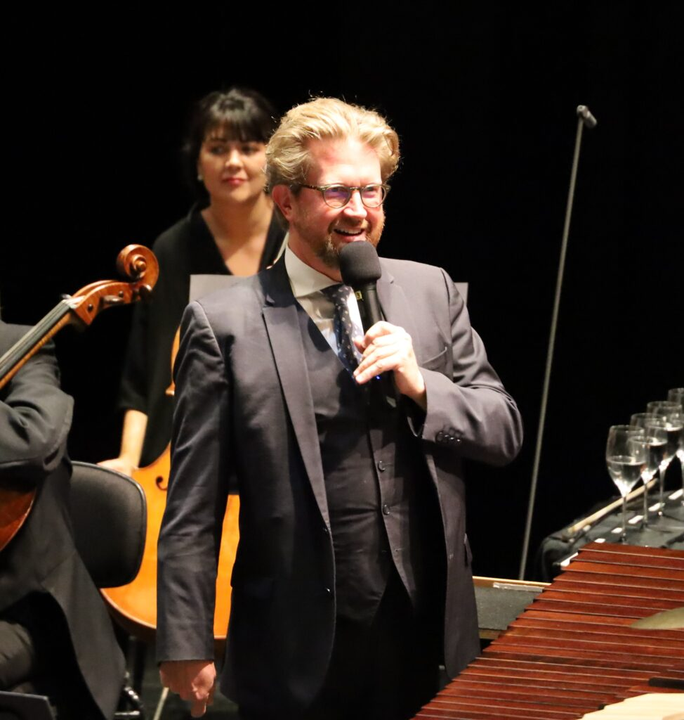A man onstage wearing a 3-piece suit holds a microphone, flanked by cello players from the orchestra behind him