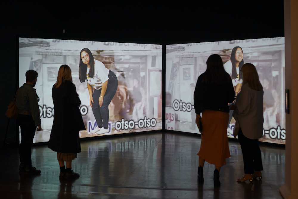 """There are two video screens. In one, Alexa Malizon poses with her hands on her knees, looking at the camera with a comical expression on her face, in the other she is laughing but we can't see her body because two visitors to the gallery block our view. Two more visitors stand in front of the first screen. There is text on both screens that appears to say """"Mag Otso Otso"""" but it is blocked both by the viewers and by Malizon's feet."""