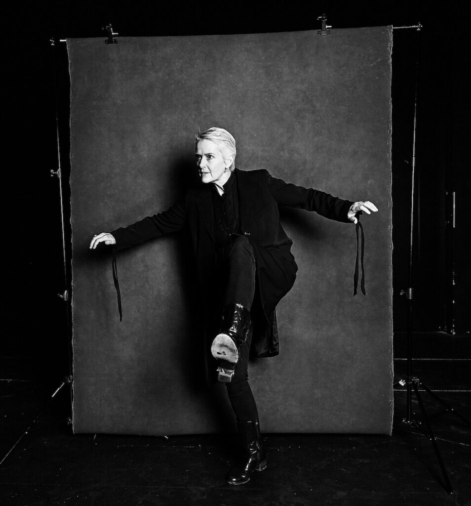Sally Richardson stands in front of a photographer's backdrop. She has one leg raised and bent, as though she is about to take a step over an obstacle, and her arms are stretched out for balance. The image is black and white.