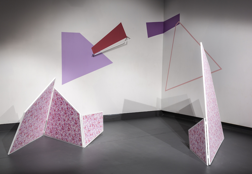 Angled three-dimensional shapes decorated in pink and purple florals stand in the corner of the gallery. On the walls are painted geometric shapes in similar colours.