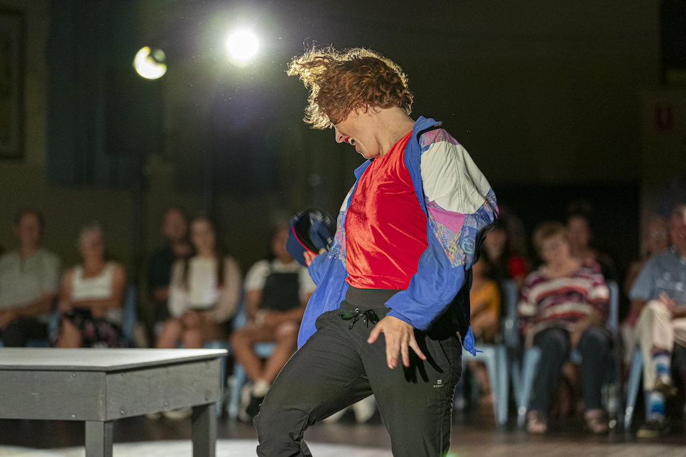 Natalie Allen is captured mid-action - she's twisting slightly to the left of the frame and her hair flairs slightly with the movement. Although her arms are close to her sides, her fingers are extended and she looks like she might be calling something out. She wears a gaudy parasilk trackie top over a red shirt and black pants.