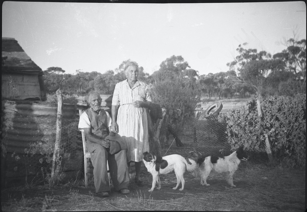 An elderly First Nations man sits on a chair, in front of a chicken wire fence. Next to him stands an elderly First Nations woman. They are on a farm - in the background you can see a paddock and the corner of what could be a farmhouse. Two dogs are at their feet and behind them is some corrugated iron, leaning against the fence.