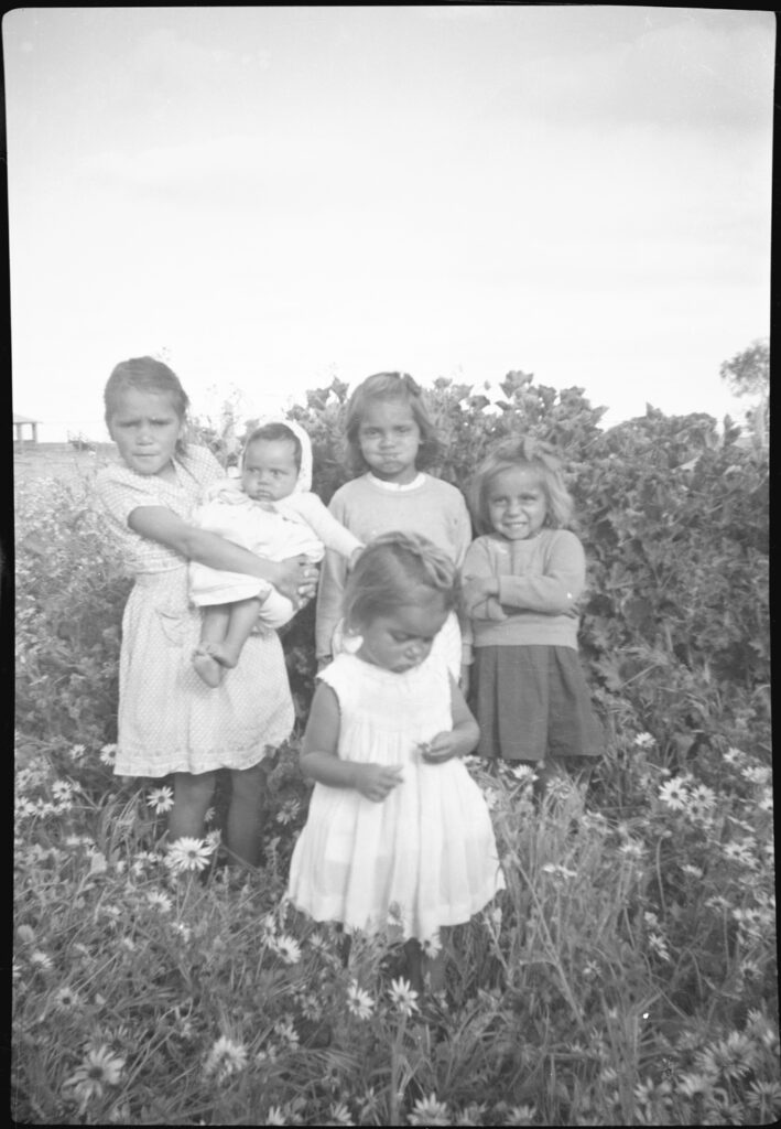 A group of five children stand in a field of daisies. The oldest, who looks about 8, holds the youngest, a baby. At the front a toddler is looking at a flower in her hand. They look happy.