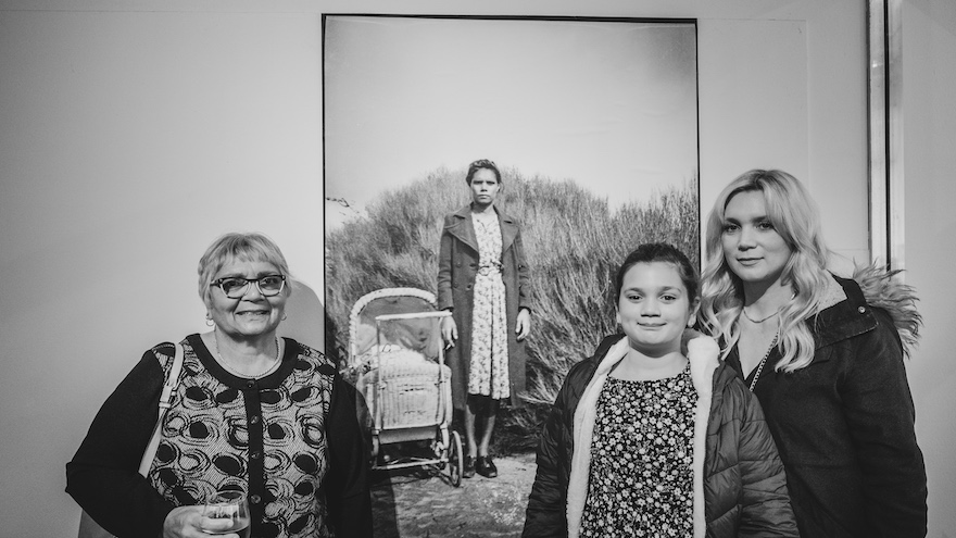 An older woman, a young woman and a child stand around a photograph of a young woman with a pram that looks like it was taken in the 1930s.