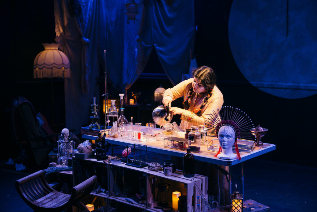 Performing in MoR , Dureshawar Khan stands at a table, surrounded by bric-a-brac that includes chemistry and medical equipment, although the backdrop of curtains and a lampshade implies that she is in a domestic setting.. She pours a cup of tea.