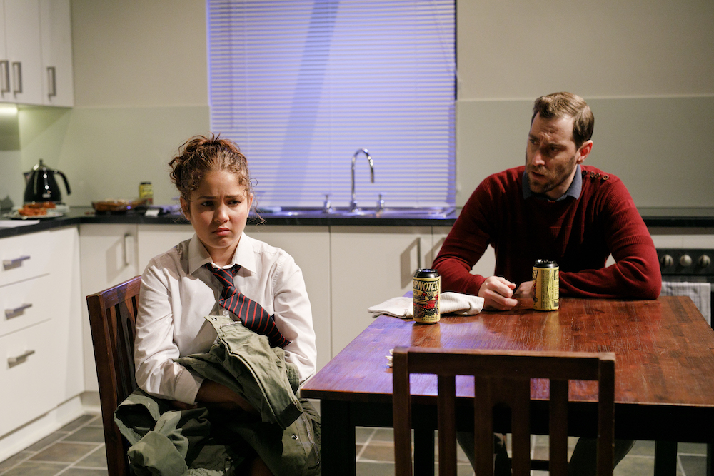 Coutney Henri, as Lucy, and St John Cowcher, as Rhys, sit at a kitchen table. He looks at her with concern and some anger. She looks away from him, in a classic expression of teen sulkiness.