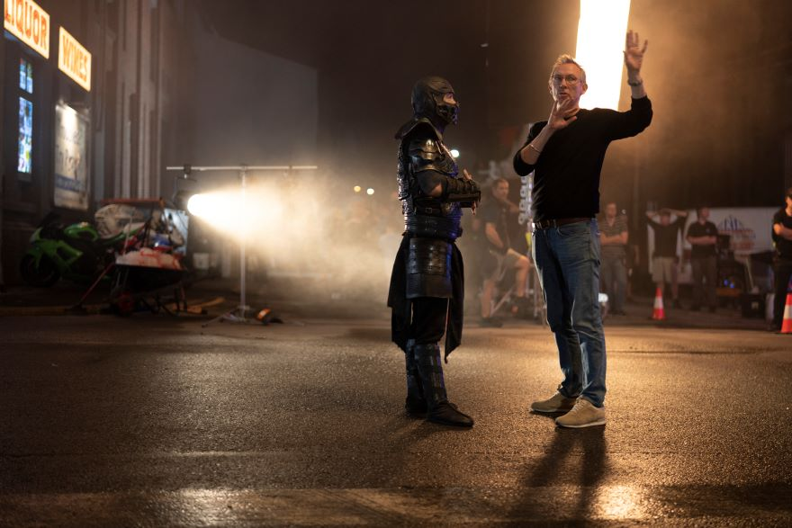 two men stand on a film set, tarmac lit by spotlights