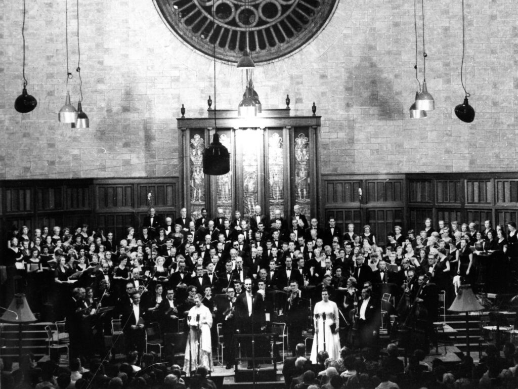A black and white archive photo of a large choir standing on a stage with two soloists
