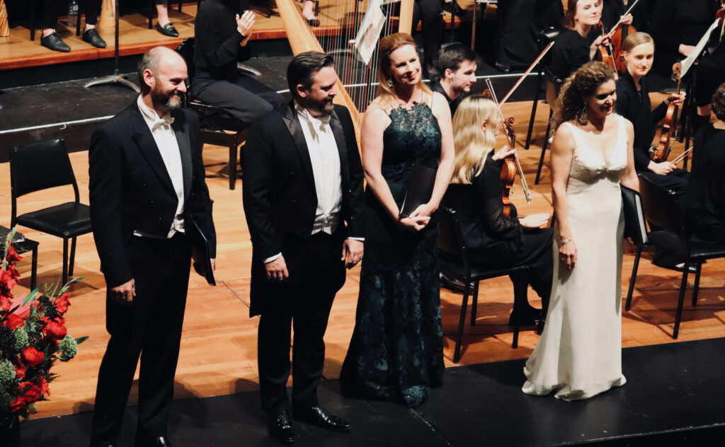 Four singers in concert dress stand smiling in front of an orchestra