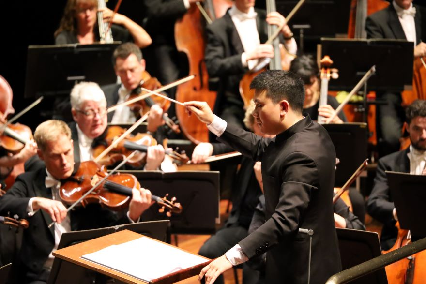 A man with a baton in his  upraised hand stands facing an orchestra of musicians