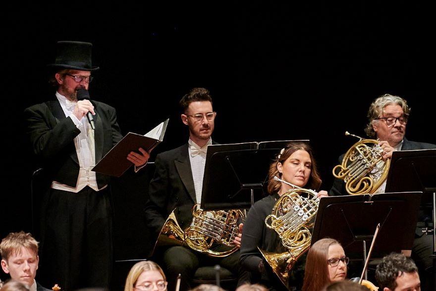 a man in a top hat holds a microphone as he stands next to three horn players