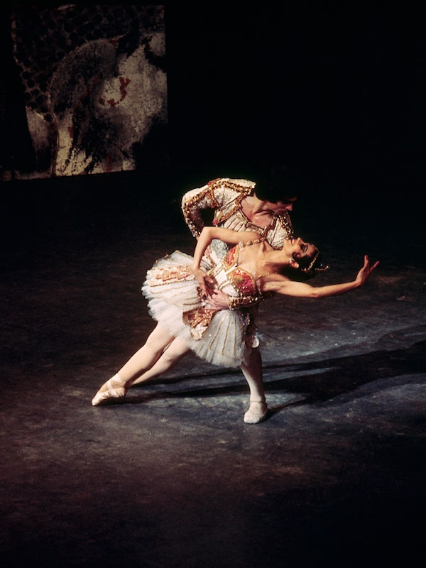 A photograph of Rudolf Nureyev, holding Lucette Aldous as she leans back off pointe. She is wearing a sparkling tutu, he wears and equally flamboyant jacket. Her arm is raised in 5th position and she smiles up at him, while he smoulders back.