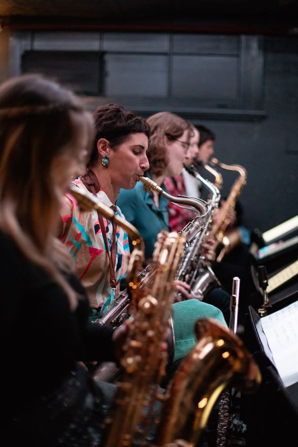 A row of female musicians playing saxophones