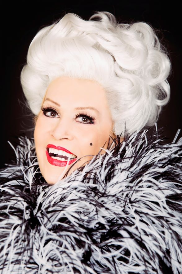 A person made up with makeup, white elegant wig and feather boa smiles at the camera