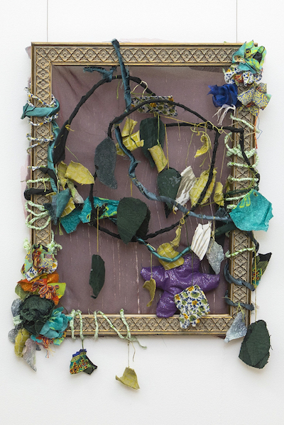 Brightly coloured fabric leaves and flowers form a creeper that wraps and winds within and around a picture frame.